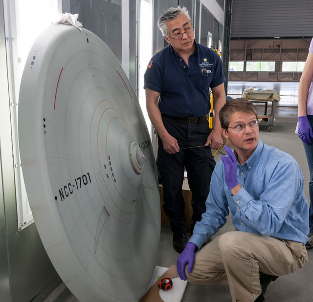 Engen Conservation Chair Malcolm Collum and Will Lee discuss the markings on the bottom of the saucer section before the model is reassembled.