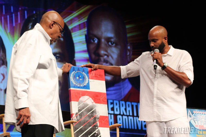 Cirroc Lofton presents Avery Brooks with a piece of art