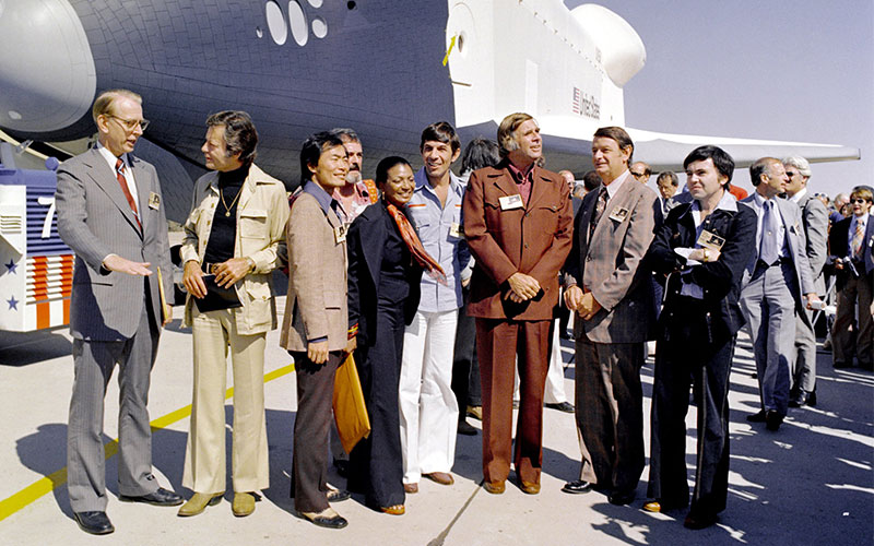 """Standing with NASA's first space shuttle """"Enterprise,"""" Nichols, Star Trek creator Gene Roddenberry, and members of the original series cast at the shuttle's rollout ceremony in 1976."""